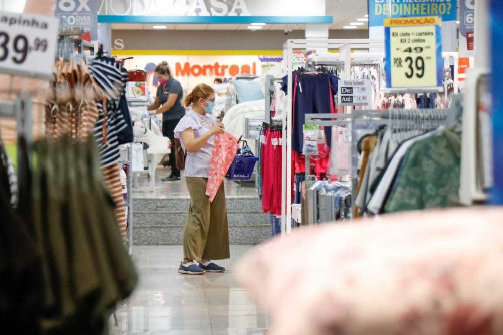 De máscara, mulher observa roupa em loja da Capital (Foto: Henrique Kawaminami)